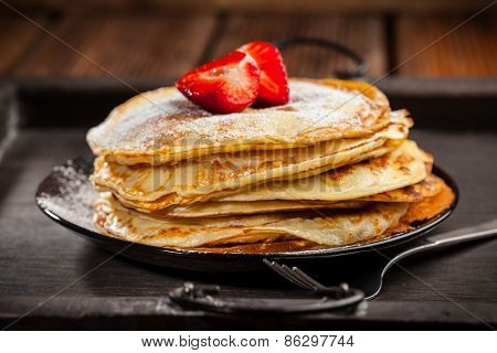 Pancakes or crepes with fresh strawberries and powdered sugar