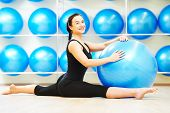 pic of do splits  - woman doing split with fitness ball during pilates stretching exercises in sport club - JPG