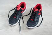 foto of flat-foot  - Running shoes with red trim flat on the floor - JPG