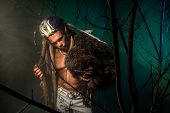 stock photo of werewolf  - Werewolf with a skin on his skin and long nails among tree branches - JPG