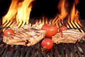 image of rib eye steak  - Two Rib Steaks Tomato and Mushrooms Roasted Over Flaming BBQ Grill - JPG