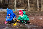 foto of daycare  - little boy and toddler girl playing with water in spring - JPG