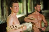 pic of seminude  - two young men stripped to waist is wrapped rope in his hands in abandoned building focus on left man  - JPG