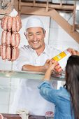 image of slaughterhouse  - Happy mature man giving packed sausages to female customer in butcher shop - JPG