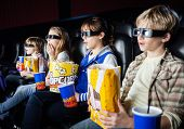 image of watching movie  - Shocked siblings having snacks while watching 3D movie in cinema theater - JPG