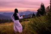 image of mystical  - Mystic woman in ancient dress alone in a beautiful romantic sunset landscape - JPG