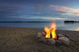 stock photo of sparking  - Camp fire on sandy beach - JPG