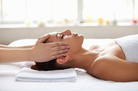 stock photo of therapist  - Beautiful young woman lying on back while massage therapist touching her face - JPG