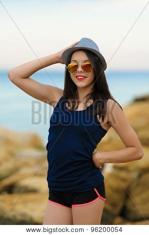 Young smiling girl in grey hat and sun glasses