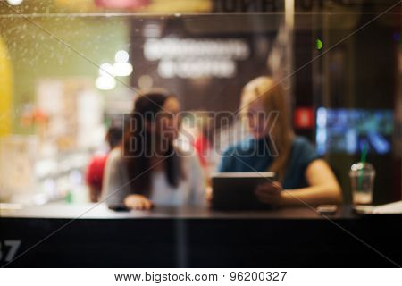Two female friends using tablet PC in a cafe