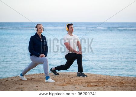 Young people listening to music and exercising outdoor