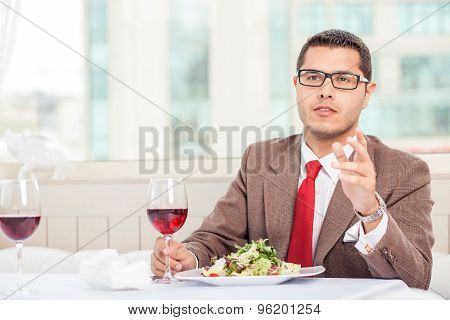 Attractive young man with suit is eating in restaurant