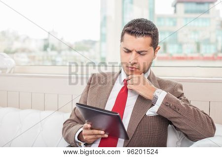 Attractive young man in suit is analyzing a project