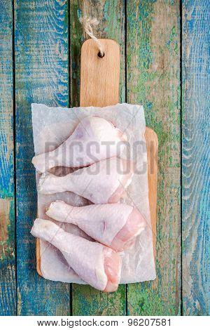 Raw Organic Chicken Legs On A Cutting Board