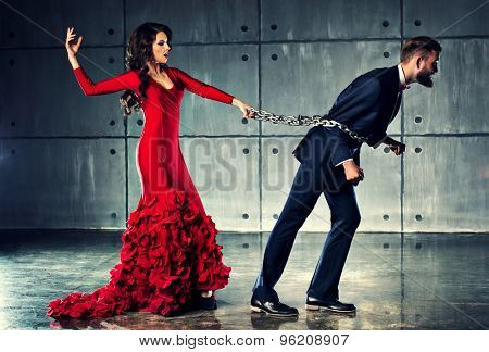 Young woman in red dress holding man on heavy chain. He tries to escape. Elegant evening clothing.