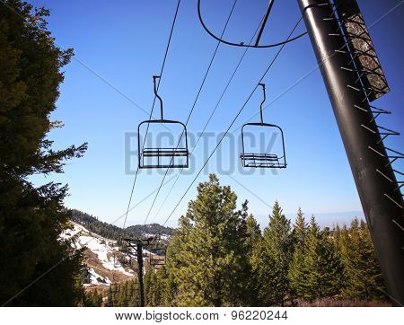Empty chairlift in ski resort. Shot in summer with green grass and very little snow