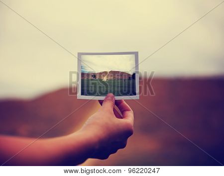a young girl holding an instant photo like a polaroid in front of a landscape that is the same but a close up instead of a wide angle toned with a retro vintage instagram filter app or action effect