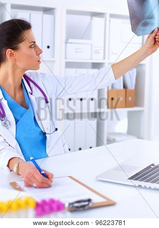 Young female doctor studying x-ray image, sitting