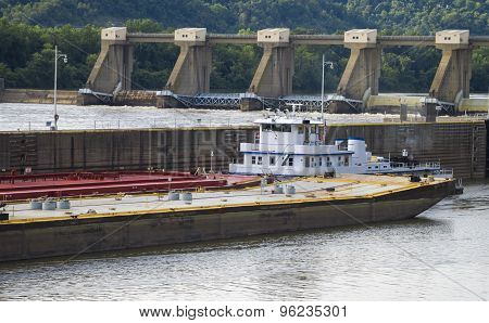 Barge with Red, Yellow and Blue in a Lock and Dam.