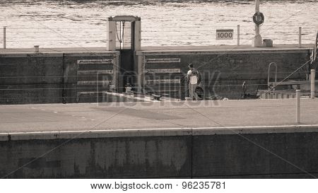 Barge Worker on Barge Lowering in Lock. Pale Sepia.