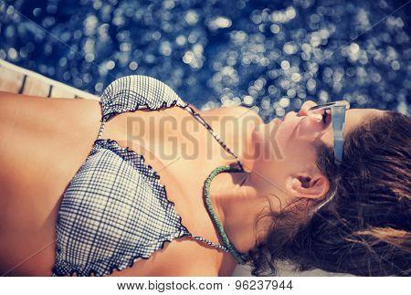 Woman tanning on the sailboat, wearing stylish swimsuit, lying down and relaxing on the board, enjoying bright sun light, spending summer vacation with pleasure