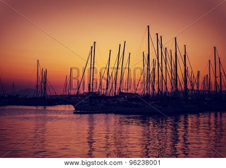Sailboat harbor on sunset, silhouettes of luxury water transport in red and yellow evening sun light, beautiful view on port in Greece