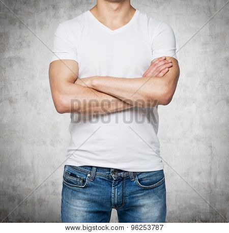 Front View Of A Person In A White V Shape T-shirt With Crossed Hands. Concrete Wall On Background.