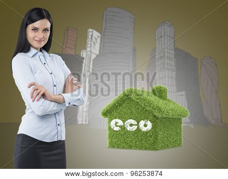 Side View Of A Thoughtful Woman With Crossed Hands. Green House And Skyscrapers Are On Background. A