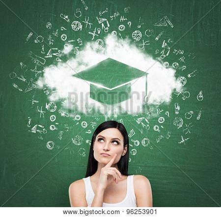 Business Woman Looking At The Cloud With Graduation Hat Over The Head. Green Chalk Board As A Backgr