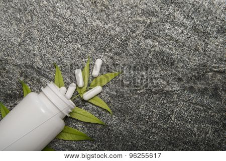 Herbal pills and bottle on green leaves on stone background