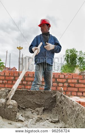 Builder man works with shovel at construction site