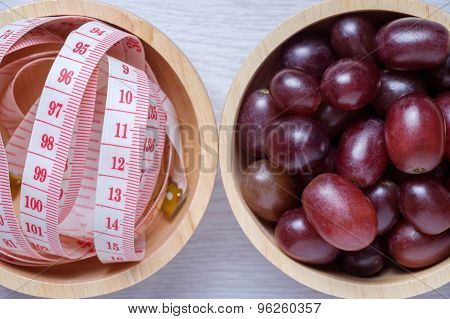 Red Grapes And Tape Measure In Wooden Bowl.