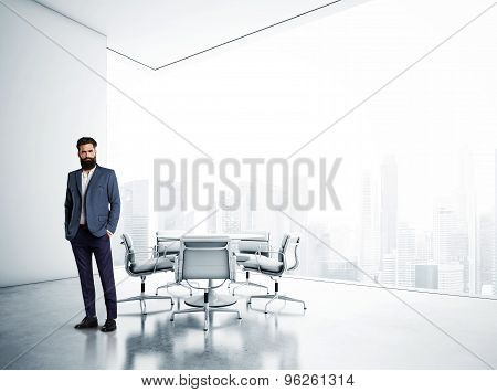 White meeting room with panoramic city view and bussines man