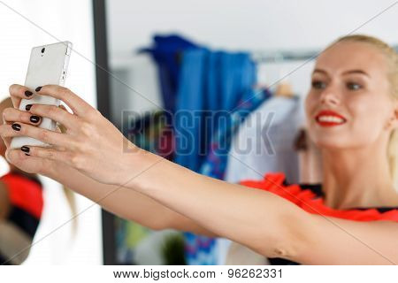 Blonde Woman Standing Near Wardrobe Rack Full Of Clothes And Mirror Making Selfie