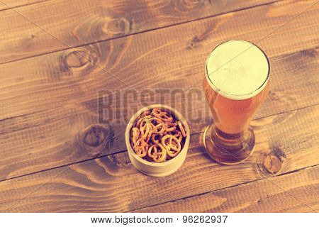 a beautiful glass of light beer on a wooden table with pretzels