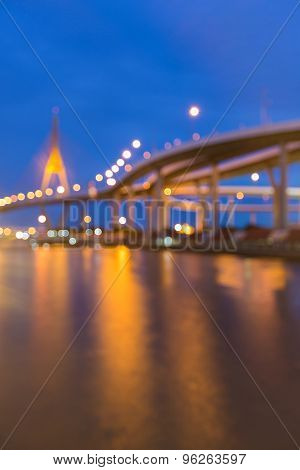 Blurred bokeh lights of City highway and Suspension bridge waterfront view