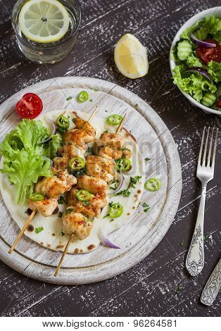 Chicken Kebabs And Fresh Vegetable Salad On A Homemade Tortilla On A Light Wooden Background