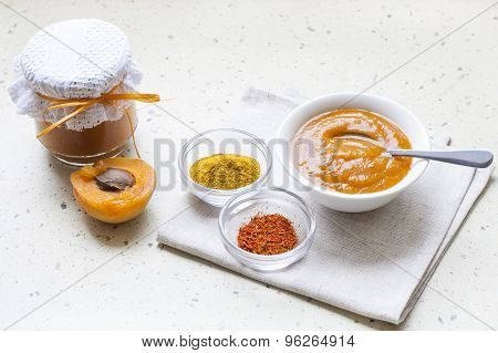 Apricot curry in a glass jar, spices and fresh apricots
