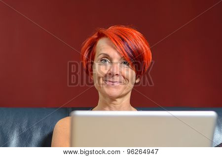 Pretty Adult Woman With Laptop Looking At Camera
