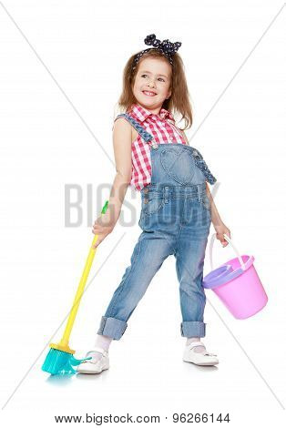 Funny little girl in denim overalls with straps holding