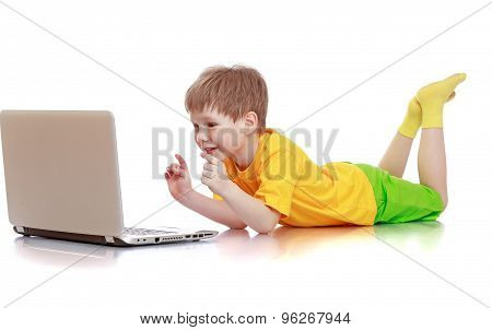 Beautiful fair-haired little boy in a yellow shirt, green shorts