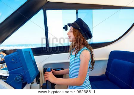 Kid girl pretending be a captain sailor cap in boat indoor holding wheel