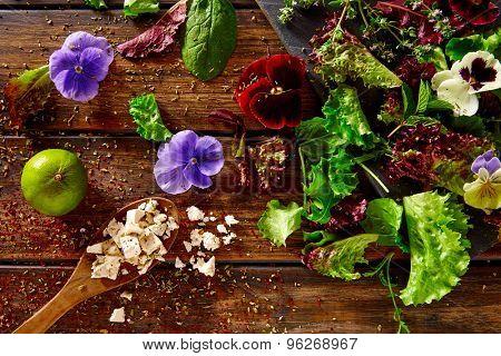Fresh salad ingredients lettuce flowers spinach feta cheese on rustic wood