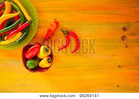Colorful mexican chili peppers habanero red in yellow wood background