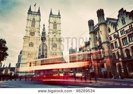Westminster Abbey church facade, red bus moving in London UK. Symbols of England, Great Britain. Vintage, retro style.