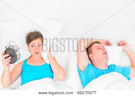 Woman With An Alarm Clock Listening To The Snoring Husband