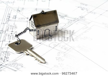 Small House Model Made Of Metal With A House Key On Architectural Drawing, Real Estate Concept