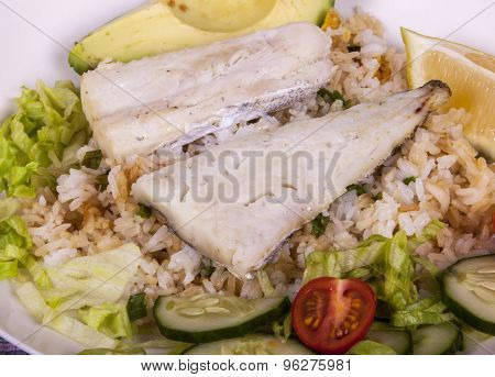 Closeup Of Baked Fish With Fried Rice And Salad