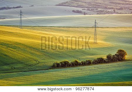 Moravian summer rolling landscape with two power line tower on sunset. Moravia, Czech Republic