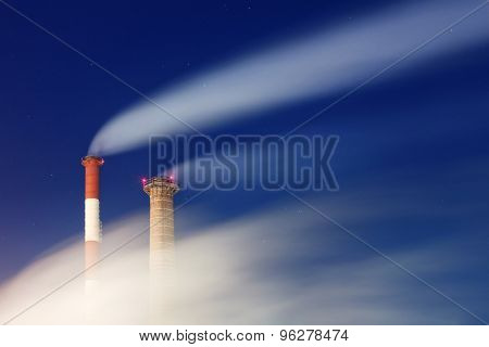 Smoking factory chimneys at night